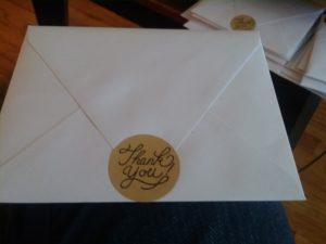 "An envelope with a sticker reading ""Thank You"" in fancy script"