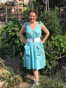 Megan standing in front of a garden, in a popover dress