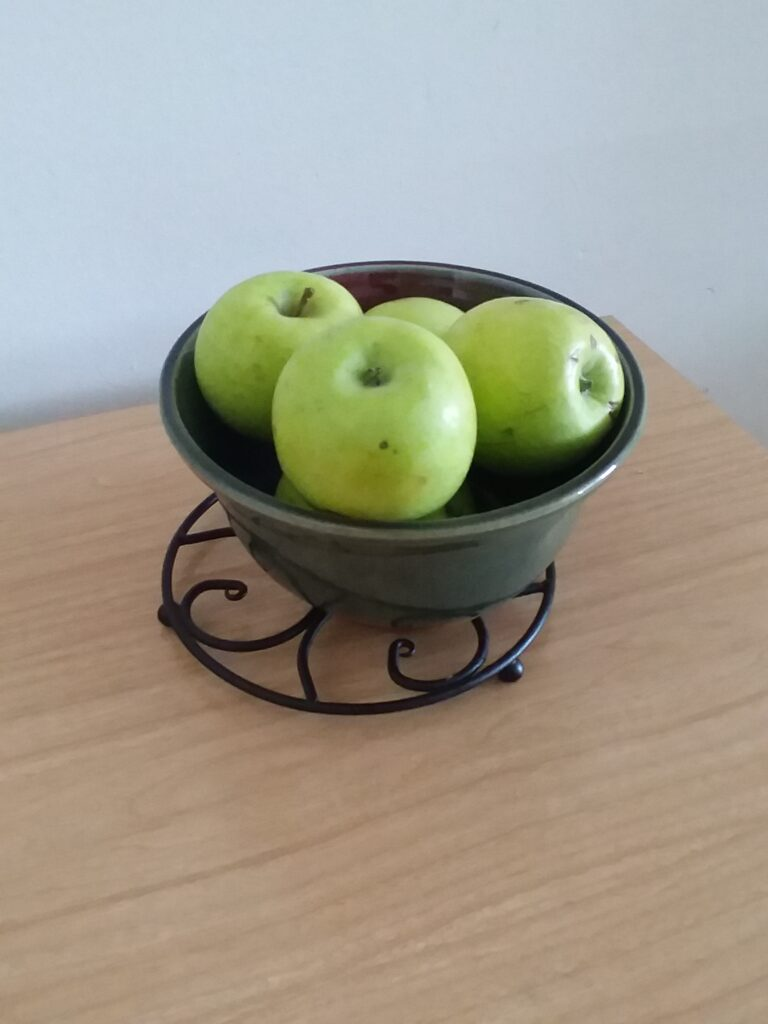 A ceramic bowl of mutsu apples on a table