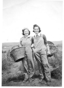 Two members of the Women's Land Army wearing overalls and sweaters carrying baskets, probably not thinking about fall vintage fashion.