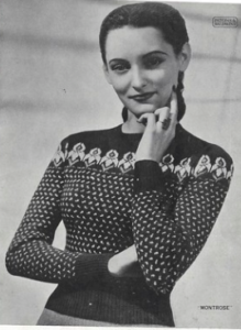 A smiling woman with dark hair, wearing a high contrast fair isle sweater with a small repeating pattern on the body, and irises on the yoke.