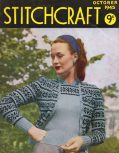 An edition of Stitchcraft magazine, October 1945. A woman with red hair and bright red lips stands modeling a light blue twinset with a black or navy snowflake or floral motif with stripes.