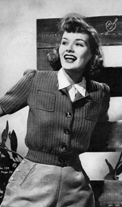 A jaunty 1940s lady leans against a fence. She wears a ribbed knit cardigan with large buttons, a fitted waist and small square breast pockets, along with side-buttoned slacks. 1940s sweater.