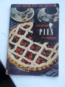 "A worn vintage pie recipe booklet ""250 Superb Pies and Pastries"" with a cherry pie and two cups of coffee on the cover."
