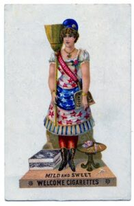 "An early 20th century ad for cigarettes, a woman dressed in patriotic clothes shoulders a broom. She wears a sash and stands on a platform. Both read ""Welcome Cigarettes"". She shoulders a broom."